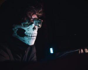 Man's face wearing skeleton mask looks ominous